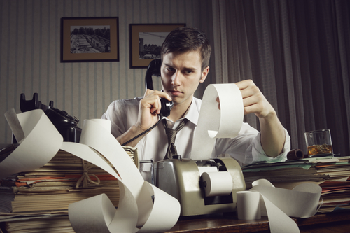 An male accountant at telephone  preparing income taxes